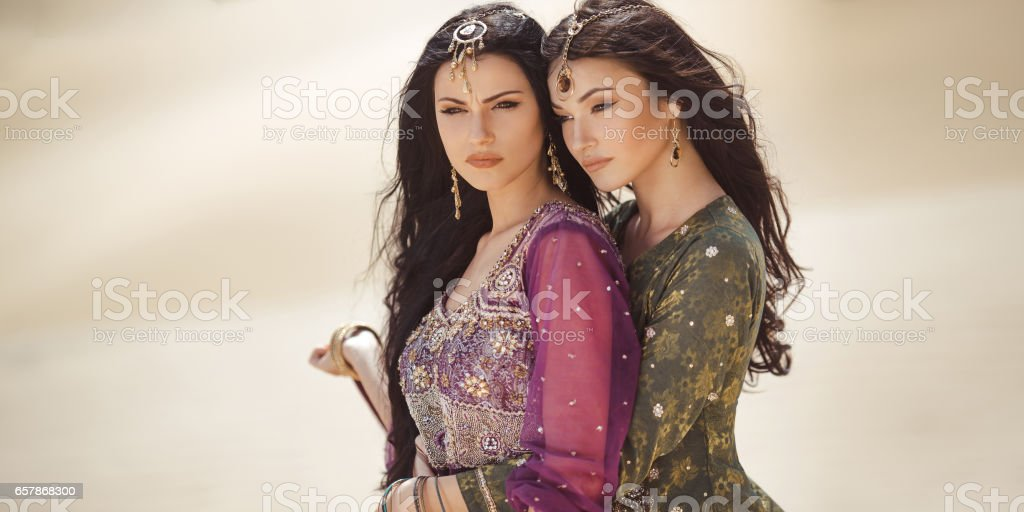 Travel concept. Two gordeous women sisters traveling in desert. Arabian Indian movie stars stock photo