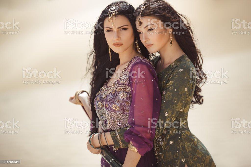 Travel concept. Two gordeous women sisters traveling in desert. Arabian girls stock photo