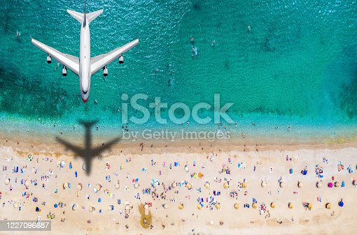 1058205304 istock photo Travel concept with an airplane flying over a crowded beach 1227096687