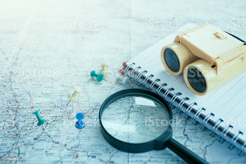 Travel concept with Magnifying glass, pushpins on map stock photo
