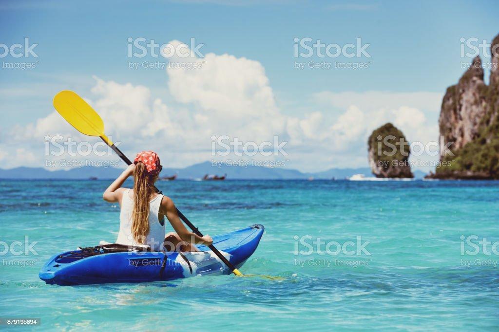 Concepto con chica sola de viaje en kayak en la bahía tropical - foto de stock