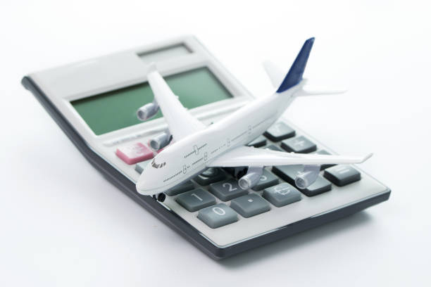 Travel cost, budget or expenses Miniature airplane model with calculator for travel budget, cost or expenses concept expense stock pictures, royalty-free photos & images