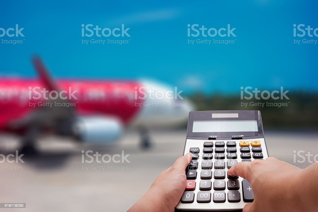Travel cost calculation concept by calculator and airplane in background stock photo