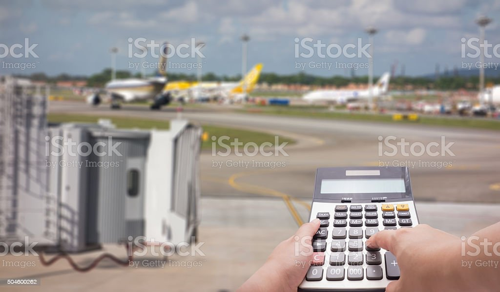 Travel cost calculation concept by calculator and runway in background stock photo