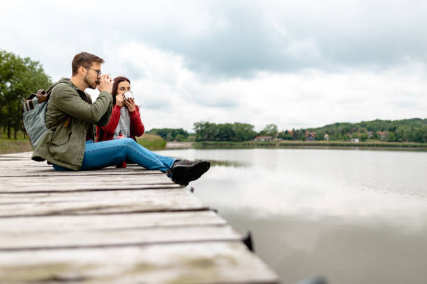 Travel couple drinking hot tea while taking a break from hiking and enjoying view from a lake stock photo