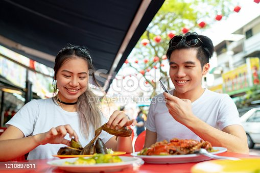 Travel couple tasting and trying local asian food