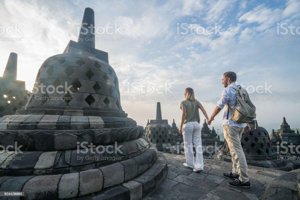 Travel couple wandering in Borobudur temple at sunrise, Indonesia stock photo