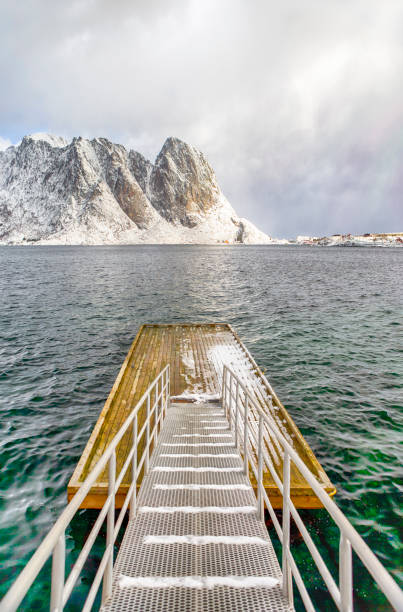 Travel Destinations. Unique Floating Bridge on Water In Traditional Sakrisoy Village in Northern part of Norway. Against Snowy Mountain Peaks.Vertical Composition