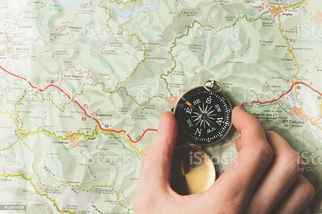 Hand holding a avigational compass on a map background