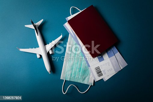 istock travel during the covid-19 pandemic. airplane model with face mask and travel documents 1268257924