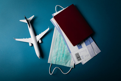 travel during the covid-19 pandemic. airplane model with face mask and travel documents