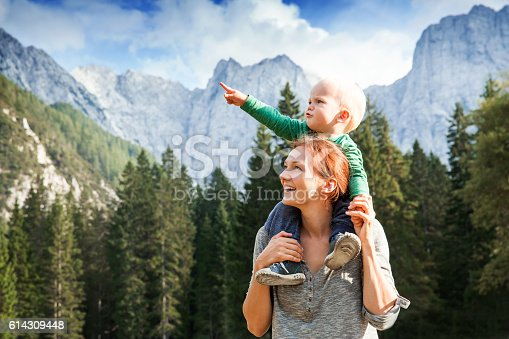 Happy mother and her child looking forward and pointing to sky. Family on trekking day in the mountains. Mangart, Julian Alps, National Park, Slovenia, Europe. Travel, Explore, Family, Future Concept