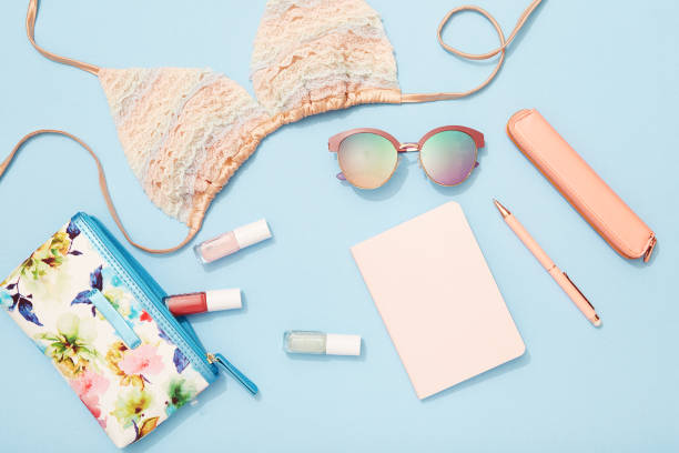 Travel flat lay on blue background with note pad, sunglasses, bikini top and nail polish - foto stock