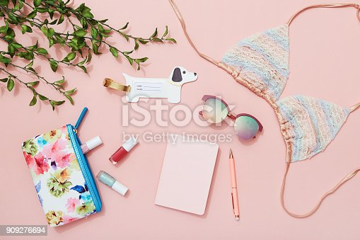 istock Travel flat lay on pink background with note pad, sunglasses, bikini top, nail polish and luggage tag 909276694
