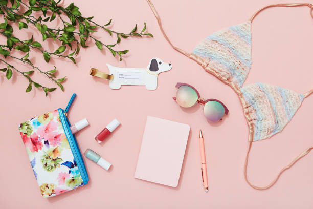 Travel flat lay on pink background with note pad, sunglasses, bikini top, nail polish and luggage tag - foto stock