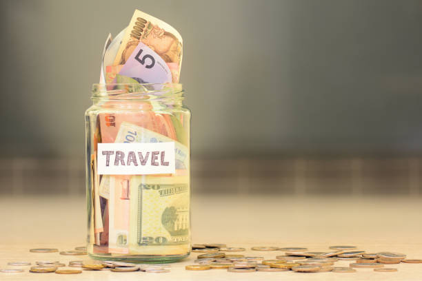 Travel funds jar full of savings with money from different countries stock photo
