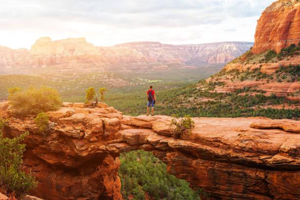 reisen sie in teufels brücke spur, mann wanderer mit rucksack aussicht, sedona, arizona, usa - canyon stock-fotos und bilder