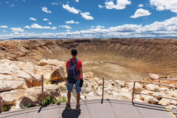 Travel in Meteor Crater, man hiker with backpack enjoying view, Winslow, Arizona, USA stock photo