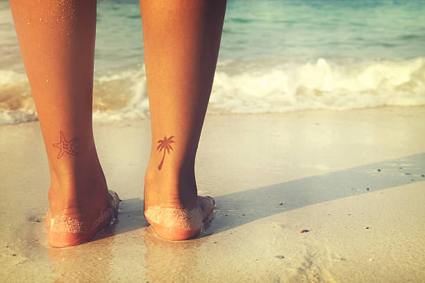 travel in summer Leisure in summer - Rear of beautiful women tan relax on beach with tattoo on foot. retro filter effect anchor athlete stock pictures, royalty-free photos & images