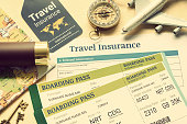 istock Travel insurance and travel security service concept : Top view of travel insurance application form, business class boarding passes, map, monocular, tag, compass, white model air plane on wood floor. 1024245892