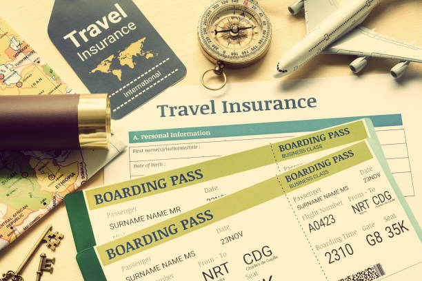 Travel insurance and travel security service concept : Top view of travel insurance application form, business class boarding passes, map, monocular, tag, compass, white model air plane on wood floor. stock photo
