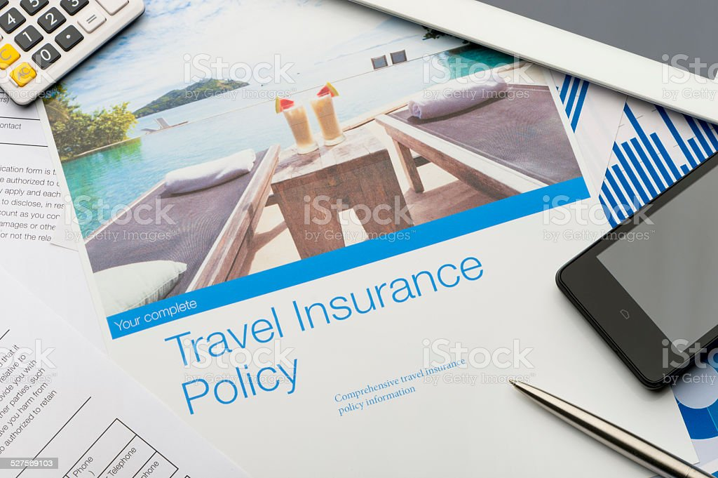 Travel insurance policy document with paperwork and technology. stock photo