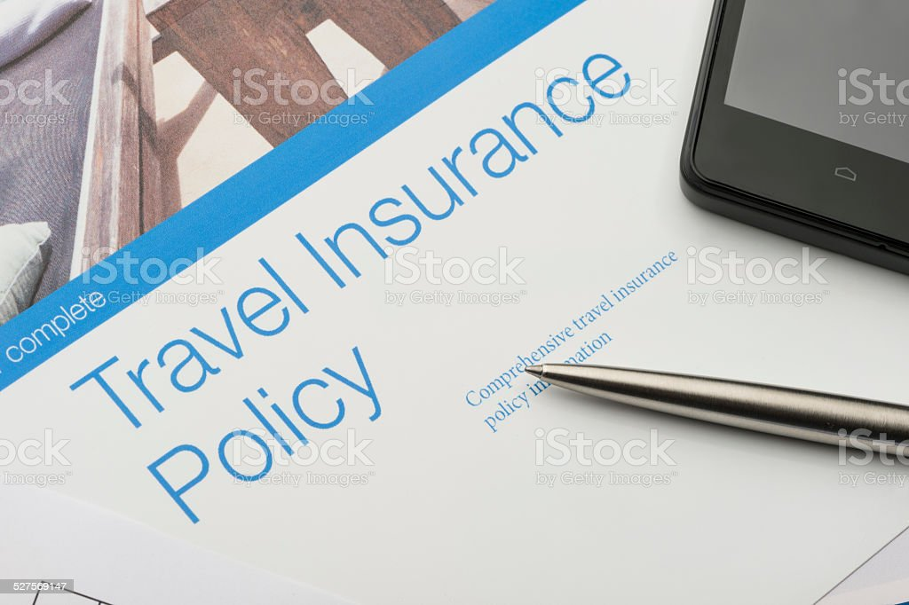 Travel insurance policy document with paperwork and technology. Peace...