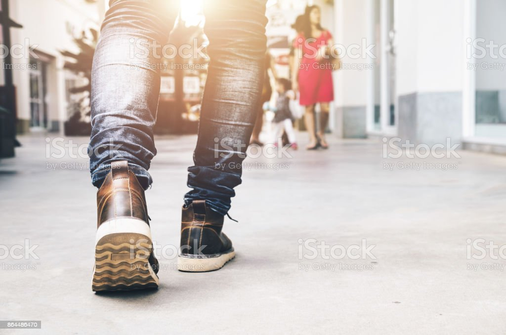 Travel Lifestyle vacations concept . Young men fashion in leather boots walk in urban city. Close up view on man's legs in blue jeans and brown leather boots with sunlight against tower building blur background for copy space. Selective focus and vintage stock photo