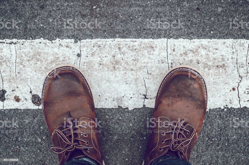 Travel Lifestyle vacations concept . Young men fashion in leather boots walk in urban city Selective focus and vintage tone. stock photo
