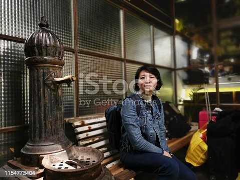 A lady relaxing at hotel bench while waiting for room check-in procedure.