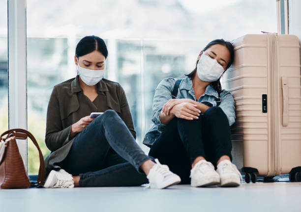 Travel looks a lot different these days Shot of two young women wearing masks while waiting together in an airport aground stock pictures, royalty-free photos & images