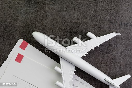 istock Travel lover special prize or honeymoon trip concept, toy airplane with 2 blank boarding pass on black texture dark black cement with copy space 922724154