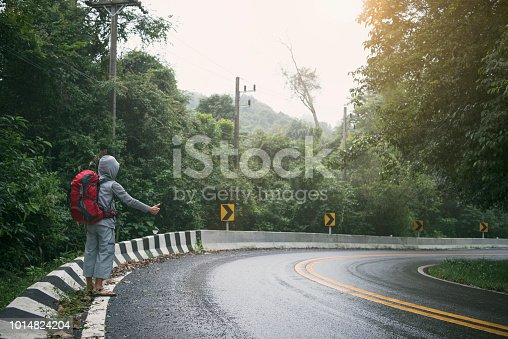 Travel man hitchhiker on road in mountain at sunset during vacation trip. concept adventure and hitchhiking.