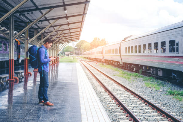 reser man med hjälp av mobiltelefon vid tågstation - waiting for a train sweden bildbanksfoton och bilder