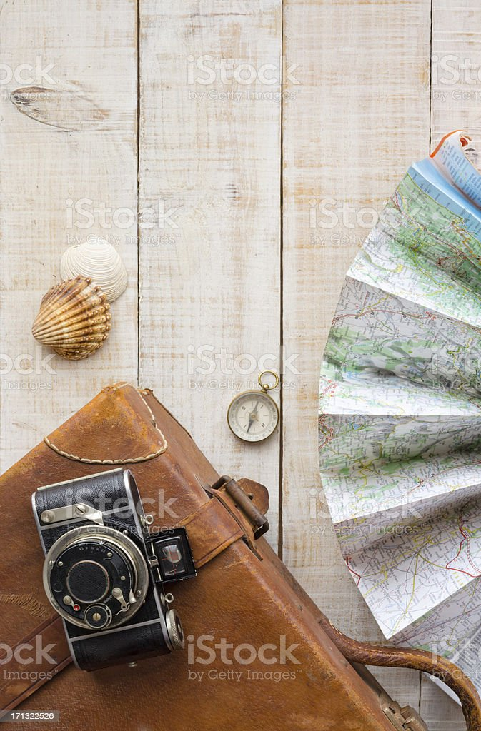 Travel objects. Suitcase, camera, map, compass and shells. stock photo