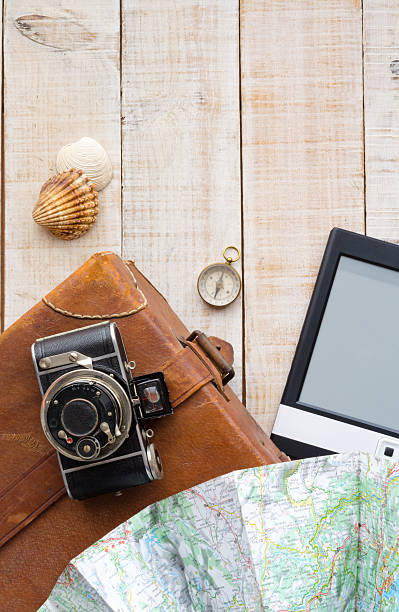 Travel objects. Suitcase, camera, map, compass, ebook and shells. stock photo