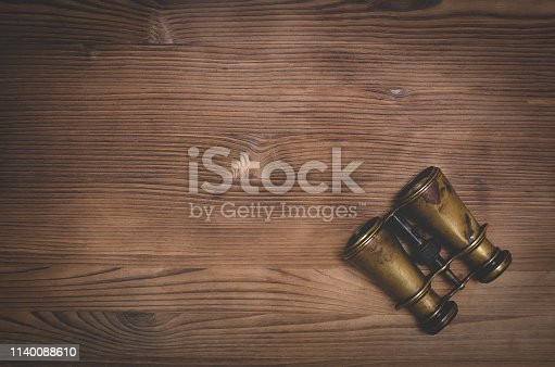 Travel or adventure flat lay background with copy space. Binoculars on a brown wooden table.