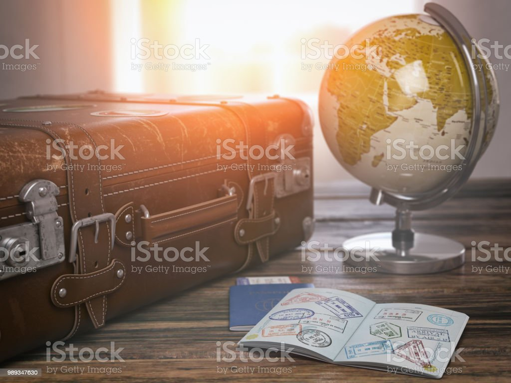 Travel or turism concept.  Old  suitcase  with open passport with visa stamps and globe. royalty-free stock photo