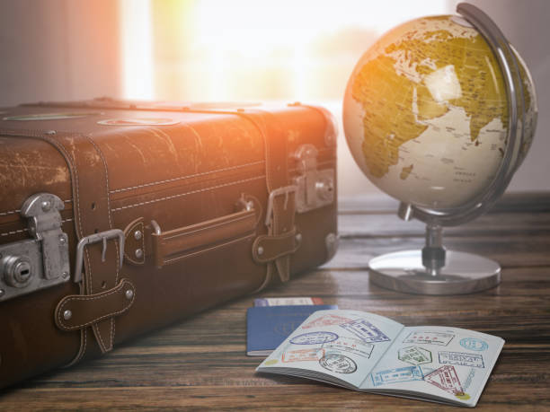 travel or turism concept.  old  suitcase  with open passport with visa stamps and globe. - destination stock pictures, royalty-free photos & images