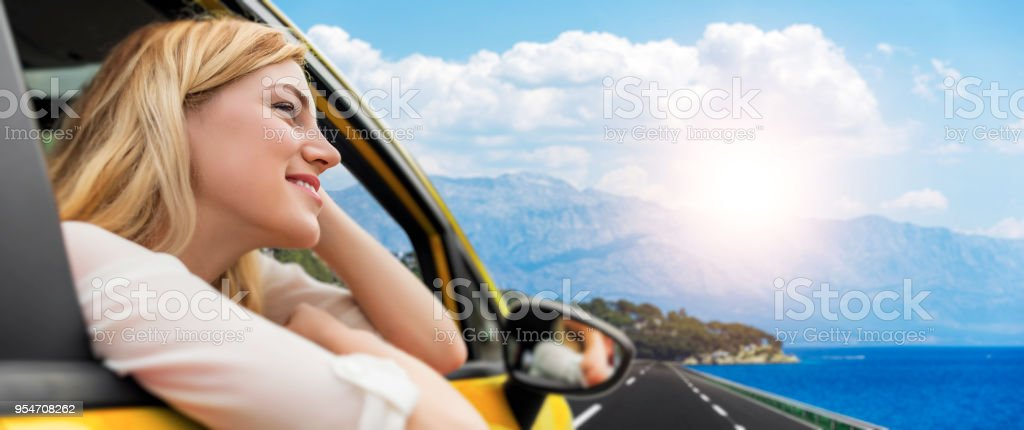 Beautiful blond girl in car on the road to the sea. Travel or...