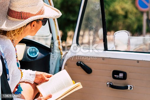 Travel people concept with young woman on passenger side in a vintage van vehicle - road trip and journey lifestyle alternative summer holiday vacation