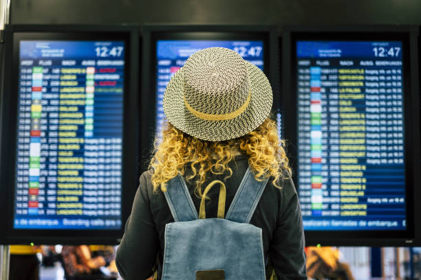 Travel people in airport or train station concept - view from rear of a blonde curly female woman with blue backpack looking and checking time departures or arrivals on the displays screen stock photo