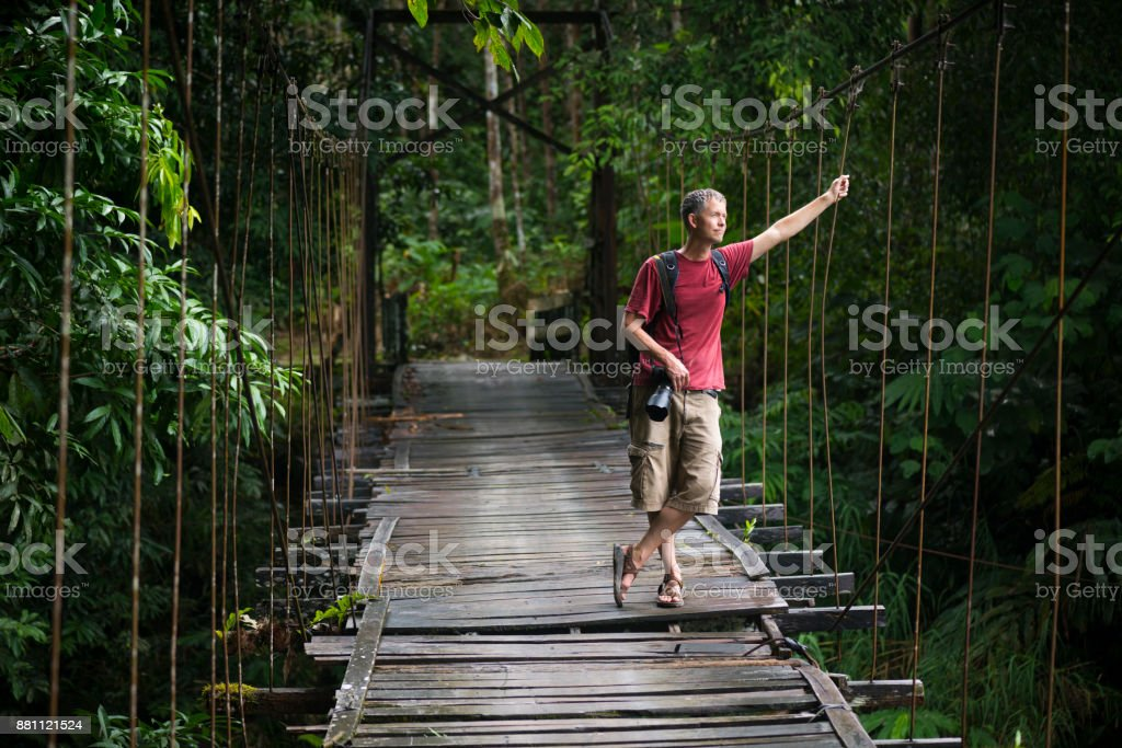 Travel photographer hiking with DSLR camera in Kalimantan, Indonesia stock photo