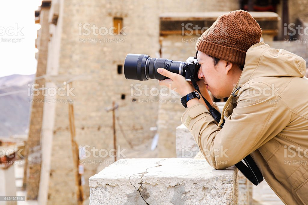 Travel photographer journalist holding a camera in mountain stock photo