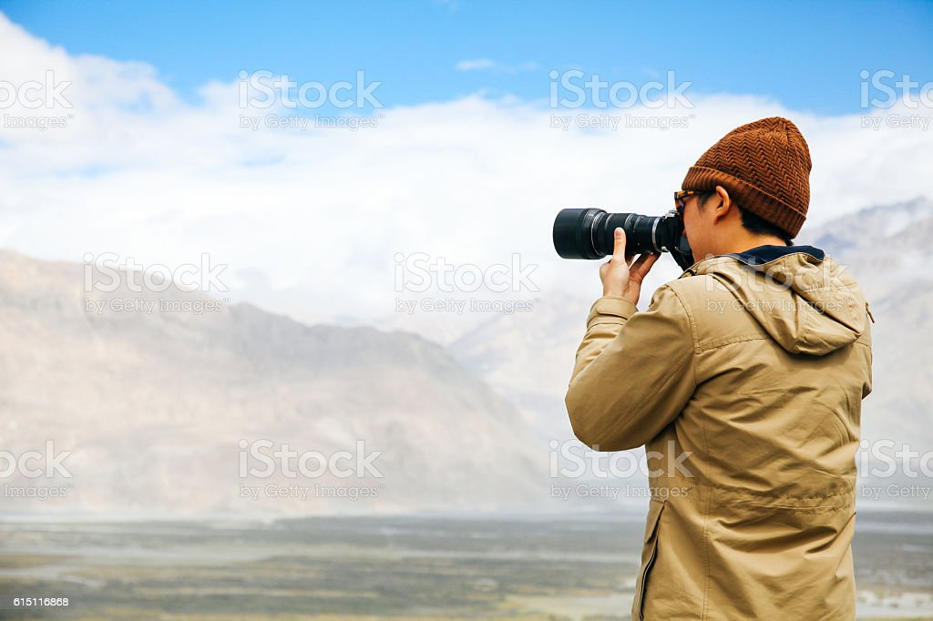 travel photographer journalist holding a dslr camera in mountain stock photo