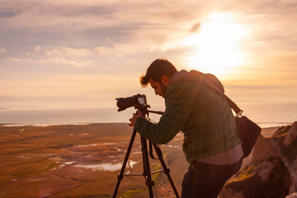 Travel photographer man taking nature video of sunset landscape stock photo