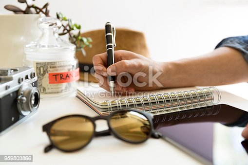istock Travel planning concept on table. Traveler's accessories and items with notebook and money saving jar, sunglasses and hat 959803866