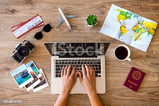 Woman using laptop and making a reservation for her travel.