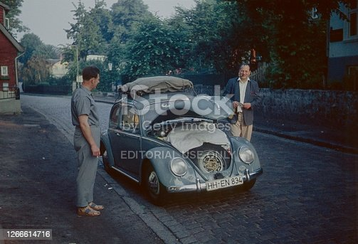 Hamburg, 1960. Two men prepare a VW Beetle for a vacation trip.