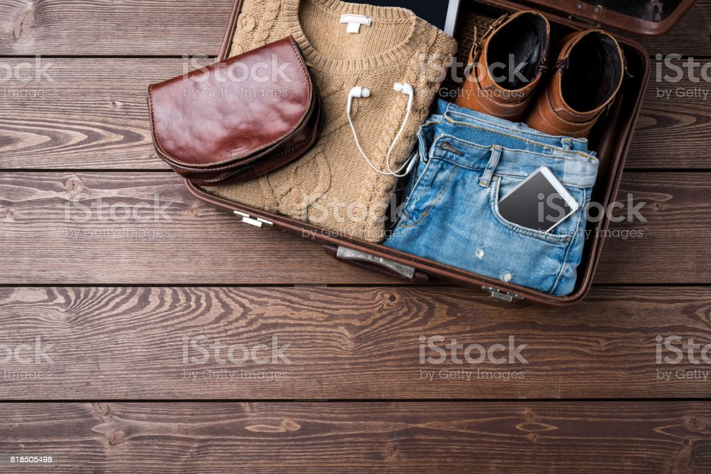 Travel preparations concept with open suitcase and woman's casual clothes stock photo